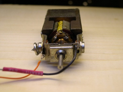 The motor has the negative tab soldered to the motor frame, which completes the electrical circuit with the locomotive frame.